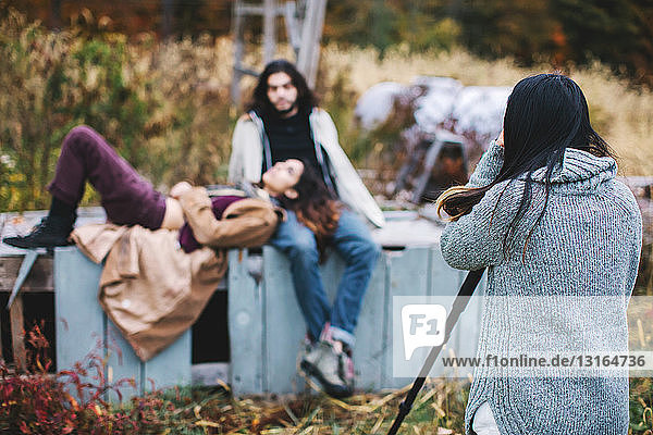 Junges Paar entspannt sich im Freien  junge Frau fotografiert sie  Rückansicht