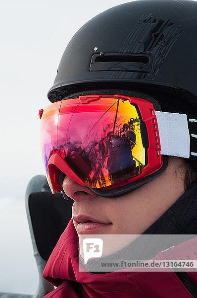 Nahaufnahme eines jungen Mannes mit Helm und Skibrille  der wegschaut