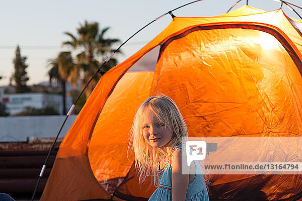 Side view of girl next to orange colour tent  looking at camera smiling