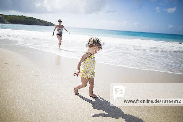 Kleinkind geht am Strand spazieren