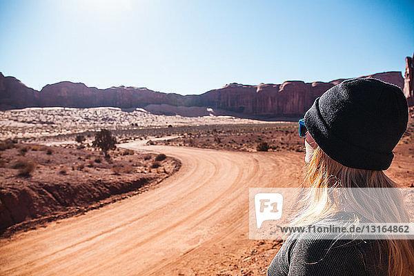 Mittelgroße erwachsene Frau  die auf eine unbefestigte Landstraße schaut  Monument Valley  Utah  USA