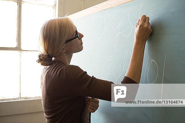 Lehrer schreibt mit Kreide an Tafel
