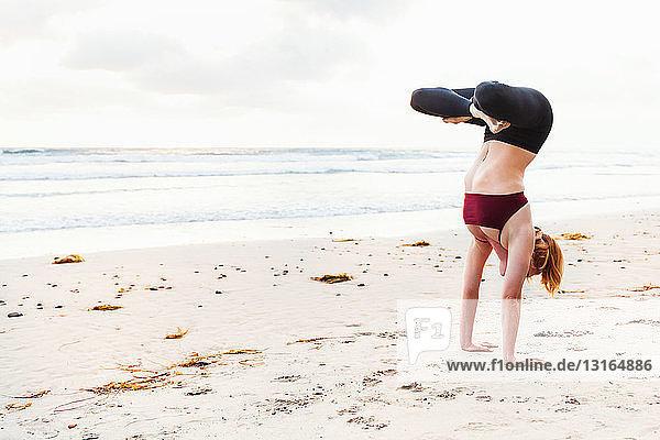 Mittelgroße erwachsene Frau kopfüber in Yogastellung am Strand