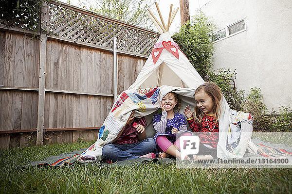 Drei junge Mädchen im Garten verstecken sich unter einer Decke