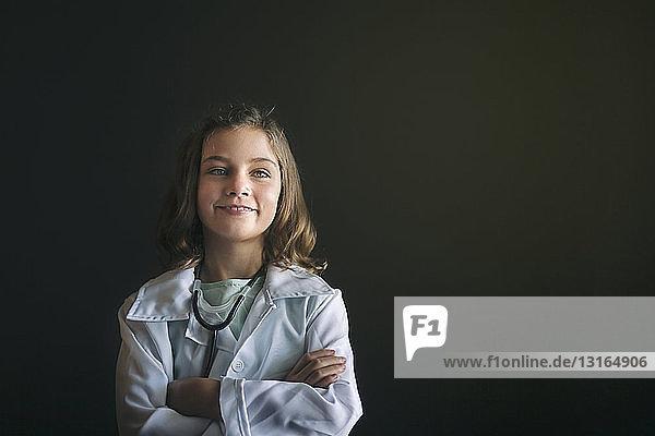 Porträt eines als Arzt verkleideten Mädchens mit Stethoskop  die Arme verschränkt und lächelnd wegschauend