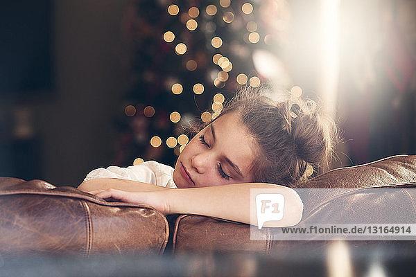 Porträt eines auf dem Sofa schlafenden Mädchens vor dem Weihnachtsbaum
