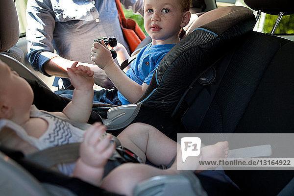 Mutter setzt zwei Kinder in Autositze