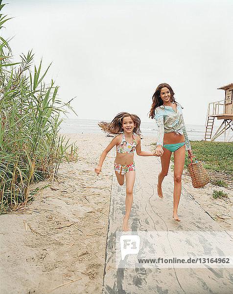 Mutter und Tochter laufen am Strand