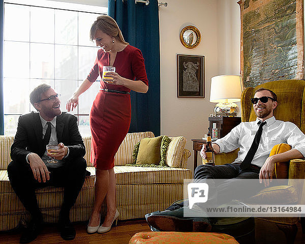 Young friends relaxing over drinks in living room