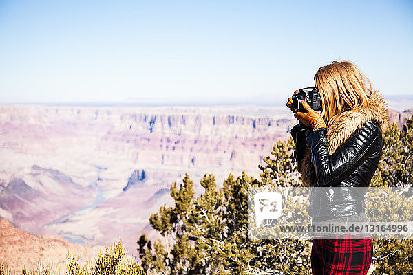 Woman taking photographs of Grand Canyon  Arizona  USA
