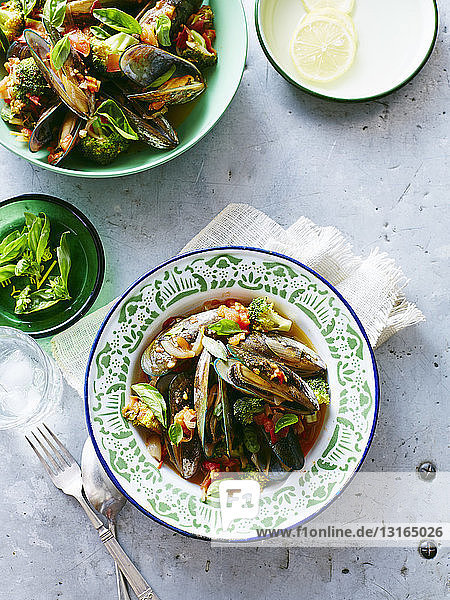 Bowls of mussels with broccoli in tomato sauce