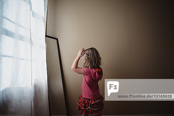 Young girl adjusting hairband in bedroom mirror
