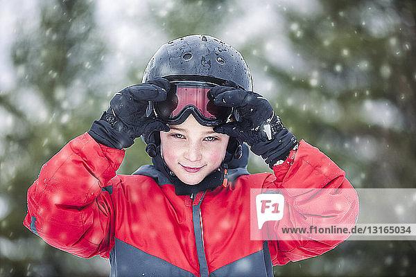 Junge mit Helm und Skibrille schaut lächelnd in die Kamera  schneit
