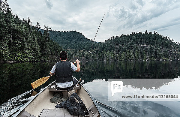 Young man fishing  Buntzen Lake  British Columbia  Canada