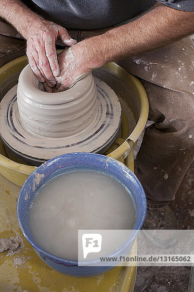Cropped high angle view of potters hands shaping clay pot on pottery wheel