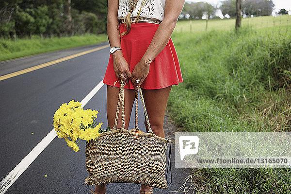 Frau mit Strohsack am Straßenrand