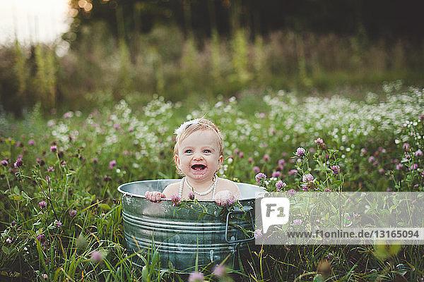 Baby girl bathing in a tin bathtub in a wild flower meadow