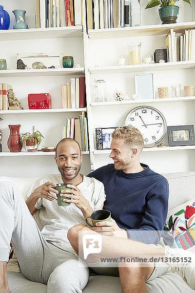 Homosexuelles Paar sitzt auf dem Sofa  hält Kaffeetassen in der Hand und schaut lächelnd in die Kamera