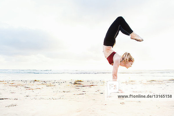 Mid adult woman practicing handstand yoga position on beach