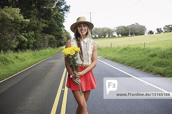 Junge Frau mit Blumen auf der Straße