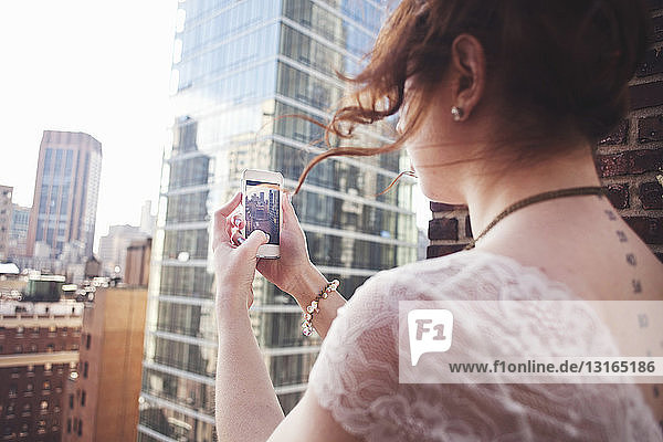 Young woman using smartphone to photograph Manhattan  New York City