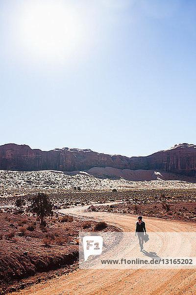 Mittelgroße erwachsene Frau  die entlang einer ländlichen Schotterstraße geht  Monument Valley  Utah  USA