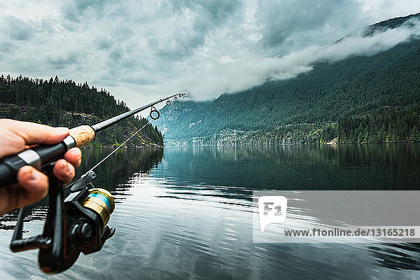 Man holding fishing rod close-up  Buntzen Lake  British Columbia  Canada