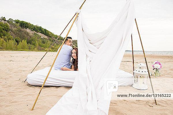 Junges Paar unter Baldachin am Strand