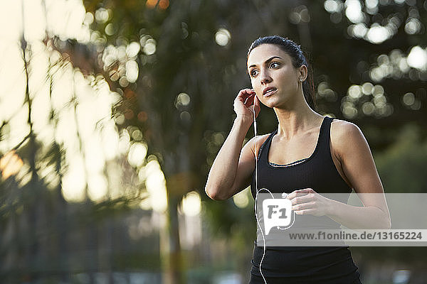 Mid adult woman putting in earphones