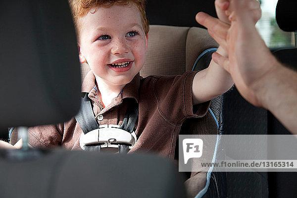 Junge im Auto  der einem Erwachsenen die Hand reicht