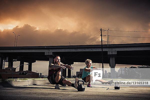 Mann und Frau trainieren auf dem Dach der Turnhalle