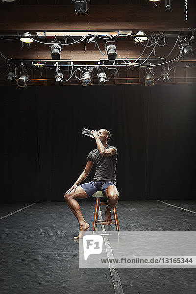 Dancer sitting on stool drinking
