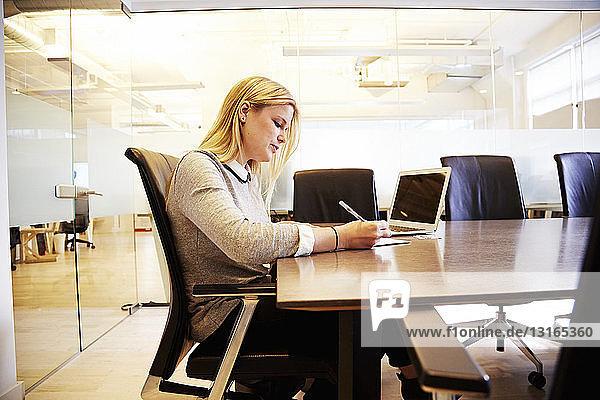 Junge Frau am Tisch arbeitend