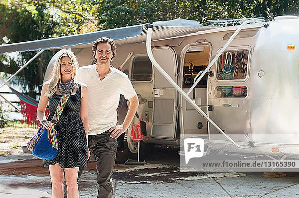 Porträt eines Ehepaares  das vor einem umgebauten Boutique-Airstream-Anhänger steht