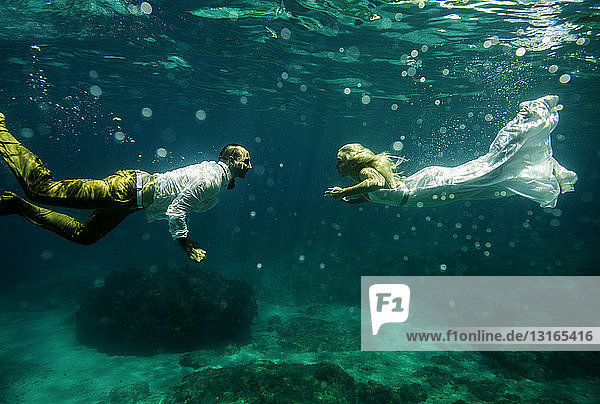 Couple in wedding attire  underwater  swimming towards each other