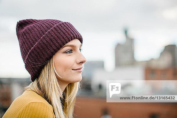 Porträt einer jungen Frau mit Strickmütze  die vom Dach aus blickt