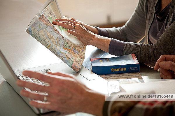 Älteres Paar liest Karte und Laptop
