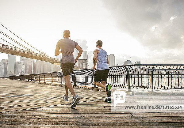Rückansicht von zwei männlichen Lauffreunden  die vor der Brooklyn Bridge laufen  New York  USA