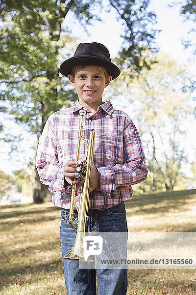 Bildnis eines Jungen mit einem Trilby  der eine Trompete in den Wäldern hält