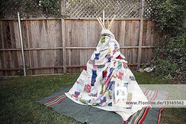 Teepee wrapped in a blanket in garden