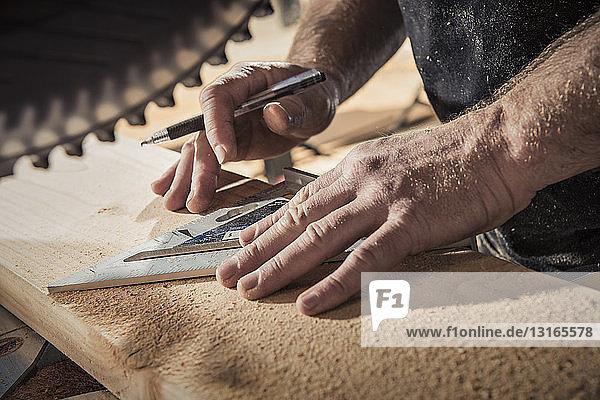 Nahaufnahme eines männlichen Tischlers mit eingesetztem Quadrat in der Werkstatt
