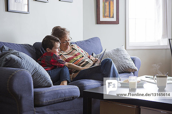 Senior woman reading book with grandson on sofa