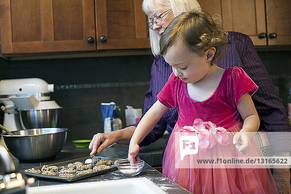 Großmutter und Enkelin backen Kekse