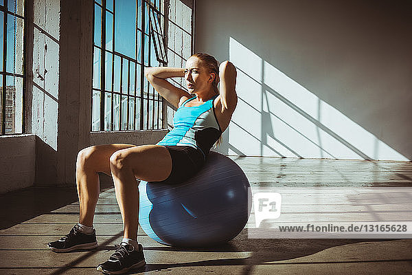 Young woman in gym sitting on exercise ball hands behind head  looking away
