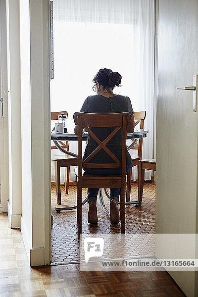 Frau beim Essen am Esstisch