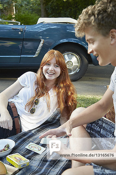 Young couple with convertible playing cards on picnic blanket