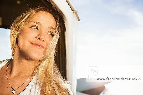 Junge Surferin schaut aus dem Fenster eines Pickup