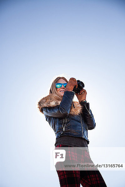 Low angle portrait of woman photographing against blue sky