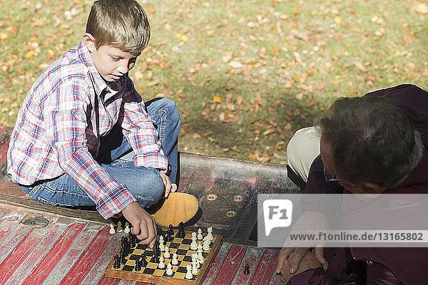 Älterer Mann und Enkel spielen Schach auf dem Rücksitz eines Pickup