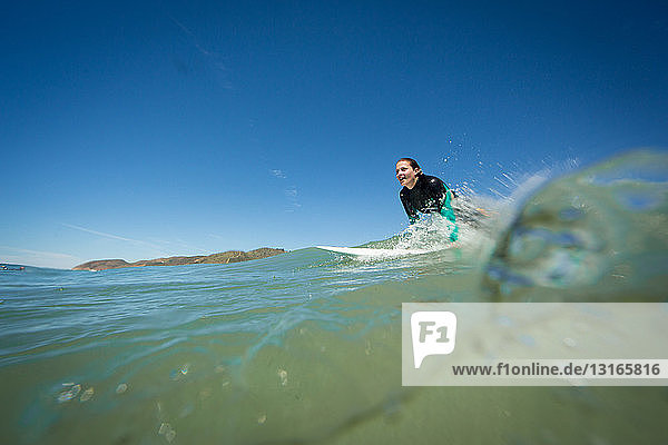 Surface level view of young woman on surfboard in ocean  Ventura  USA